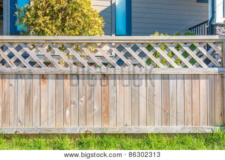 wooden fence with green lawn and houses