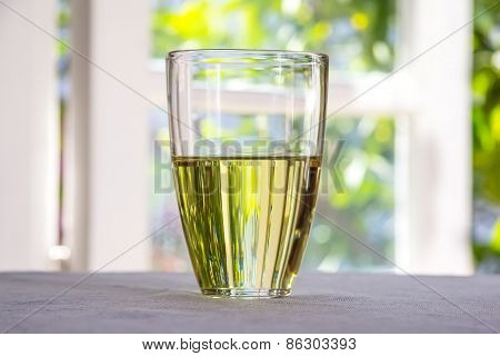 Glass With Olive Oil Placed On A Table Against The Window.