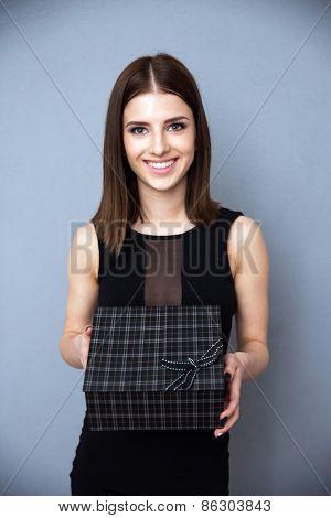 Smiling beautiful woman giving gift at the camera