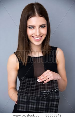 Happy elegant woman holding gift over gray background