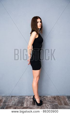 Full length portrait of attractive young woman in sexy black dress. Posing over gray wall.