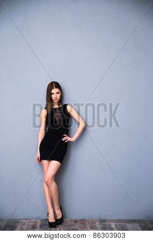 Full length portrait of a cute beautiful woman in sexy trendy dress. Posing over gray background. Looking at camera