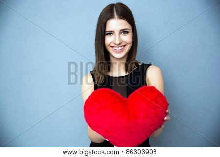 Portrait of a happy young woman in black dress standing with red heart over gray background. Looking at the camera.