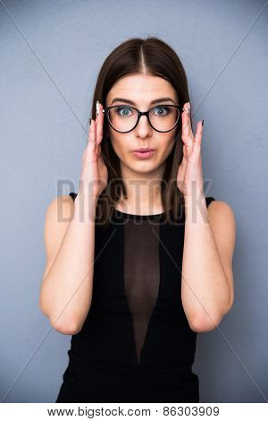 Portrait of a cute woman in glasses standing over gray background. Wearing in sexy black dress. Looking at the camera