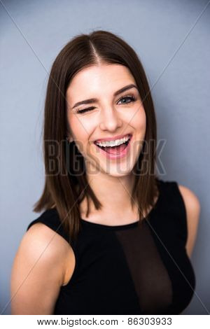 Portrait of a laughing cute woman winking over gray background. Wearing black trendy dress. Looking at camera