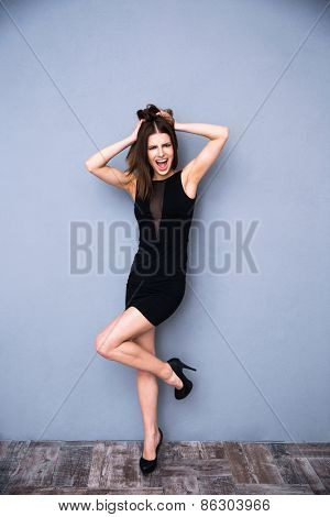 Full length portrait of a beautiful woman in trendy black dress. Posing over gray wall. Touching her hair.