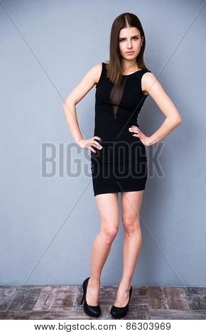 Full length portrait of a happy attractive woman in fashion black dress. Posing over gray wall. Looking at camera.