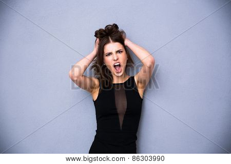 Angry young woman shouting over gray background. Wearing sexy black dress. Looking at the camera