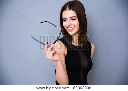 Portrait of a happy woman holding glasses and looking away. Wearing black sexy dress. Posing over gray background