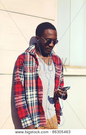 Fashion Portrait Of Stylish Young African Man Listens To Music On The Smartphone, Hipster Wearing A