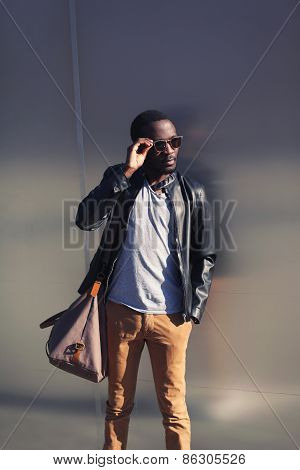 Handsome African Man In Leather Jacket And Sunglasses Against The Metal Urban Wall