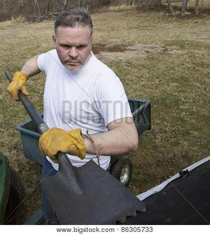 Man taking shingles off roof