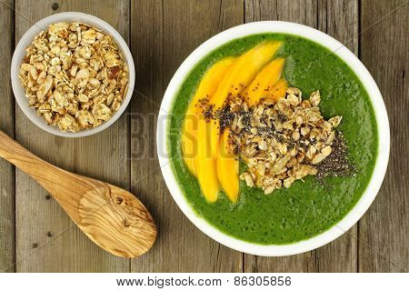 Green smoothie bowl overhead view on wood with spoon