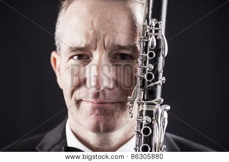 Portrait of man with striking features holding clarinet over black