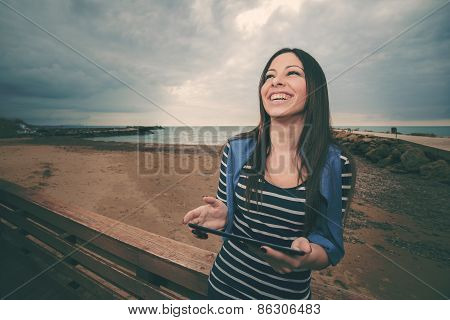Woman With Tablet Smiling In Winter Warm Filter Applied