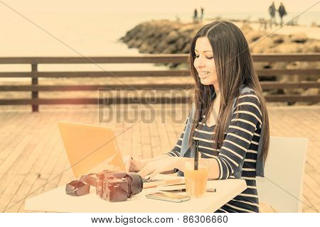 Young Woman Working On Laptop By The Sea Warm Filter Applied