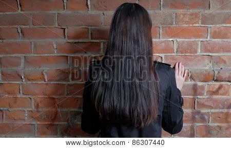 Back view of long haired brunette women against red brick wall