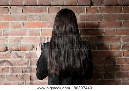 Rear view of a woman with long brown hair against red brick background