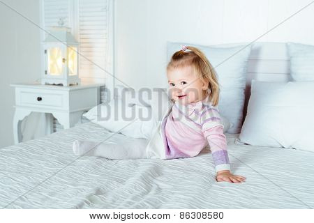 Funny And Cute Blond Little Smiling Girl Playing On Bed In Bedroom
