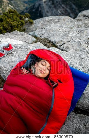 Woman in sleeping bag on the mountain