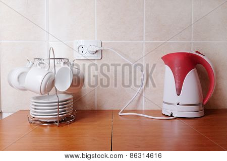 White coffee cups with saucers and electric kettle