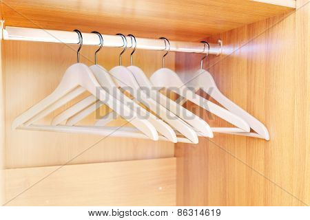 Wooden hanger hanging in an empty closet