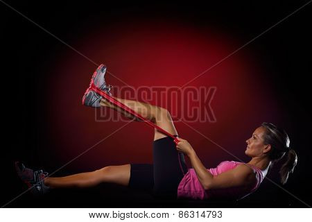 young woman exercising with elastic fitness band in the gym