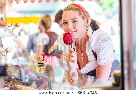 Woman eating candy apple at Oktoberfest wearing Dirndl