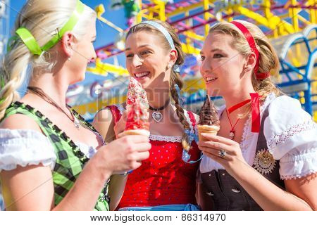 Friends visiting together Bavarian fair in national costume eating sundae ice