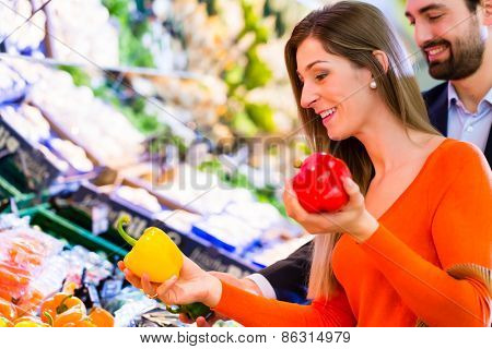 Couple selecting paprika while grocery shopping in supermarket