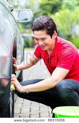 Asian man cleaning car rims with sponge