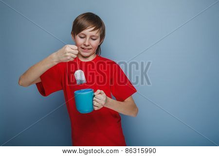 boy teenager European appearance in a red shirt brown drops tea