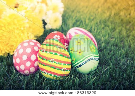 Easter Eggs with flower on Fresh Green Grass ( Filtered image processed vintage effect. )