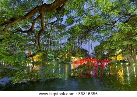 The Hoan kiem lake with the Huc bridge illuminated behind the flamboyant trees, Hanoi, Vietnam