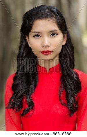 Portrait of a pretty Vietnamese woman in red Ao Dai