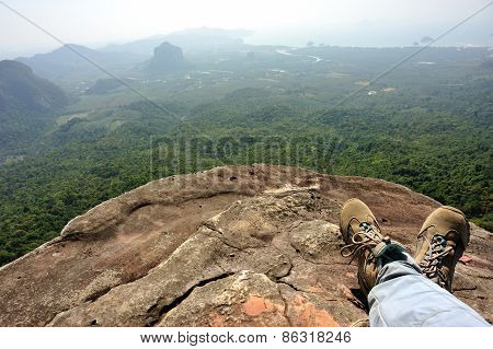 woman hiker legs relax at mountain peak cliff