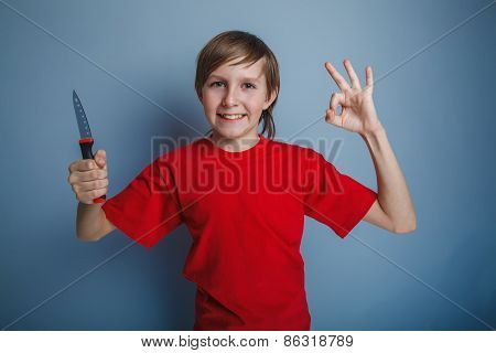 boy teenager European appearance in a red shirt holding a brown