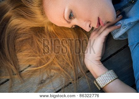 Profile fashion portrait of strict red-haired girl