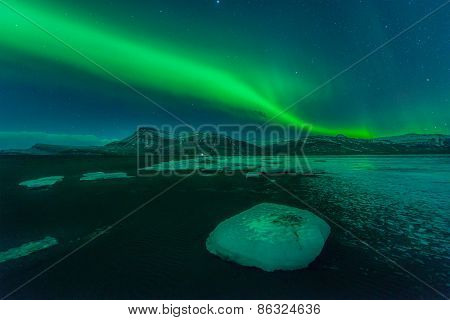 A beautiful green and red aurora dancing over the Jokulsarlon lagoon Iceland
