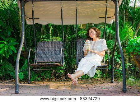 Woman drinks fresh coconut on the swinset