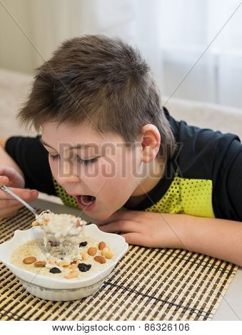 Teenager boy has oatmeal for breakfast