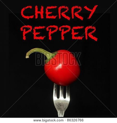 Cherry pepper on a fork on a black background