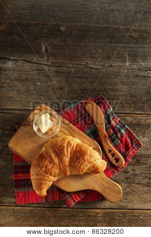 Fresh homemade croissant on a cutboard with butter and wooden knife