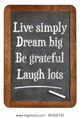 Live simply, dream big, be grateful, laugh lots. Motivational words on a vintage slate blackboard