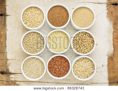 healthy, gluten free grains abstract (quinoa, brown rice, millet, amaranth, teff, buckwheat, sorghum), top view of small round bowls against rustic barn wood