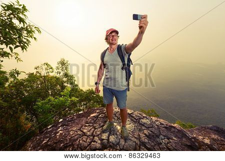 Hiker taking selfie on top of the mountain at sunrise