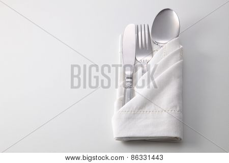 Folded napkin with fork, spoon and knife on white background