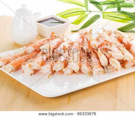Tiger Shrimps With Soy Sauce On White Plate Over Wooden Background