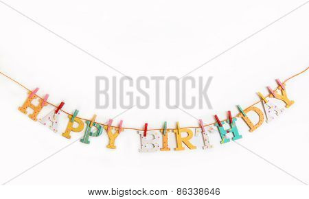 Happy birthday text with wooden letters on a white background.