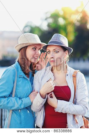Young Beautiful Woman Telling Secret To Her Friend In The City